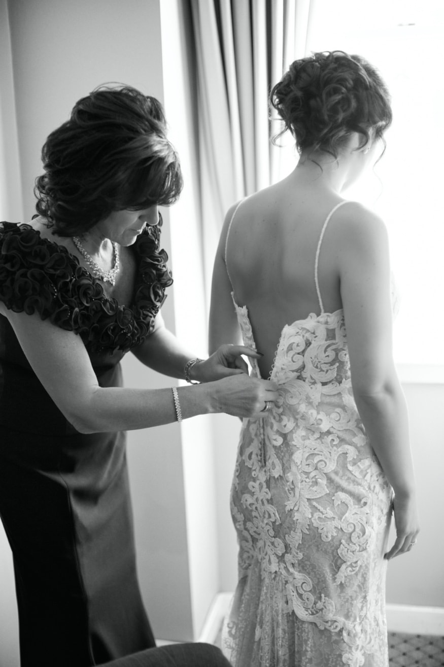 Bride getting dressed in her Maggie Sottero dress at Nassua Inn.