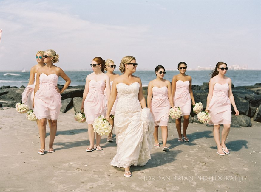 bride and bridesmaids walking beach in ocean city