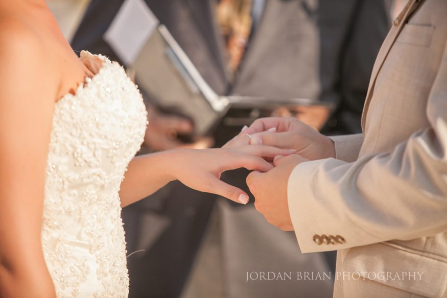 bride and groom exchange rings at beach wedding in ocean city