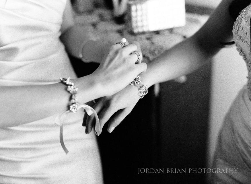 Bride putting on bracelet for wedding