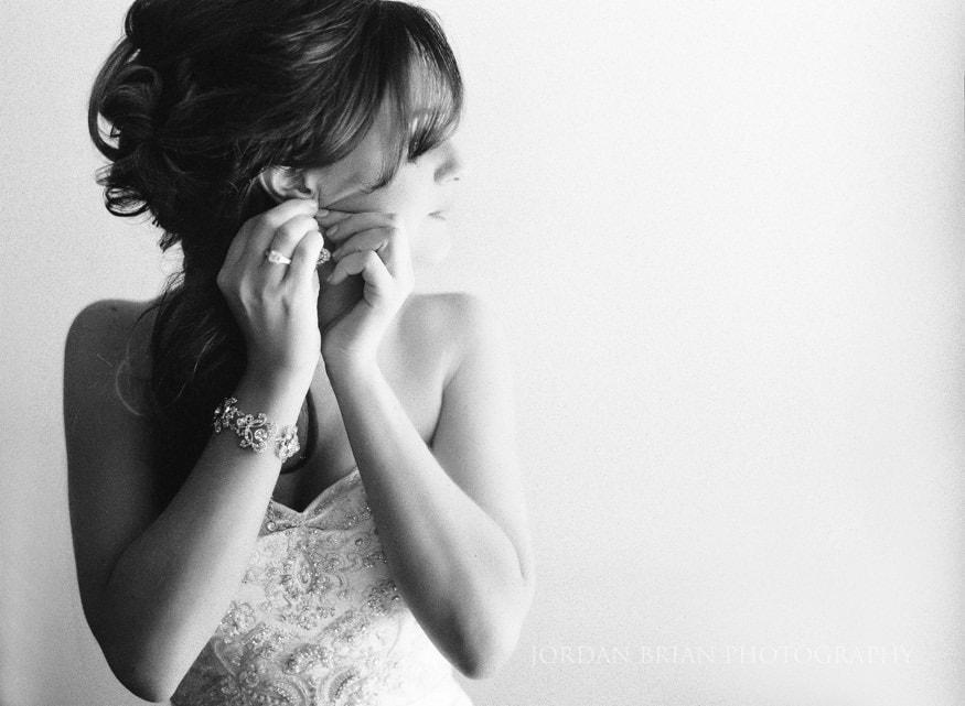 Bride putting earings on