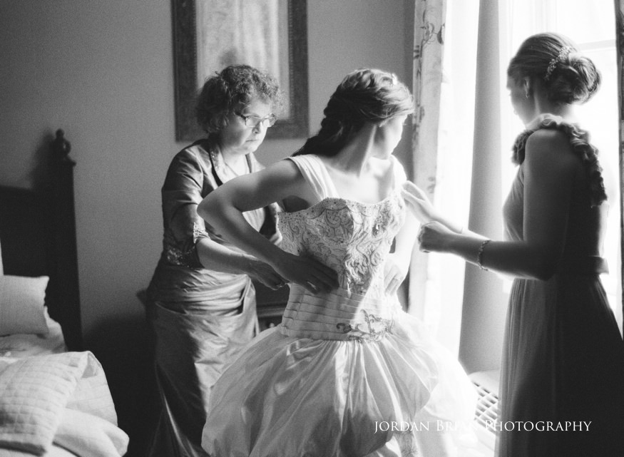 mom helping bride put wedding dress on before grounds for sculpture wedding