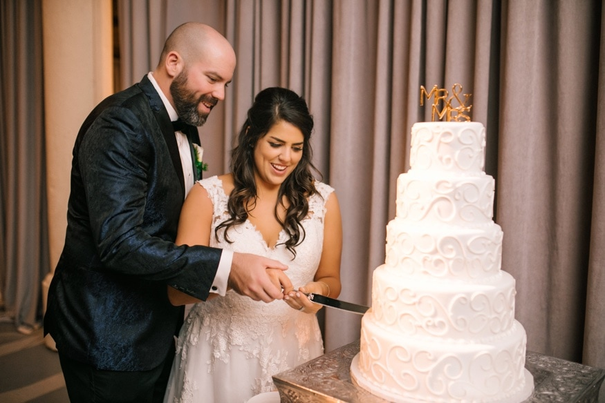 Bride and groom cut the cake from Isgro Bakery at Moulin Philadelphia wedding reception.