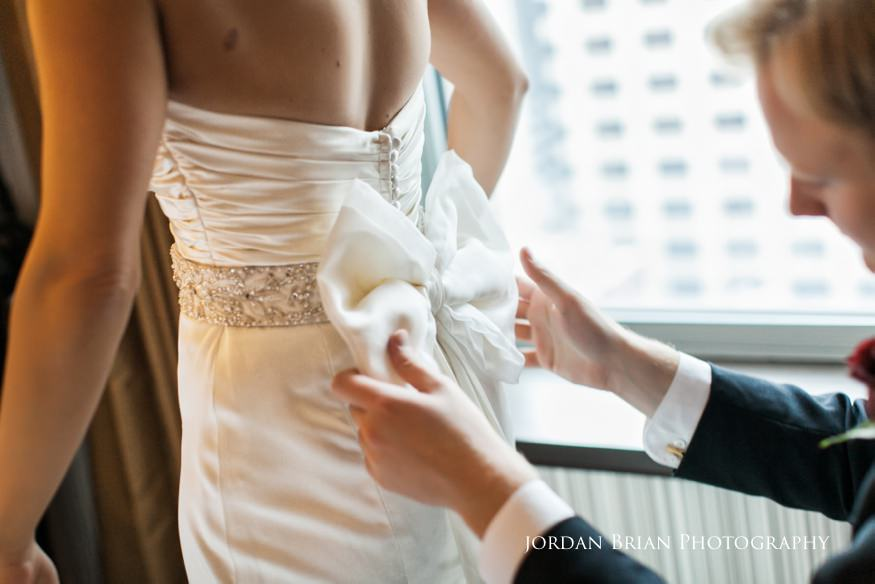 Bride fixing dress bow at Sofitel for Fairmount Park Horticulture Center Wedding