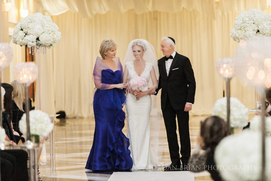 bride walking down isle with parents at curtis center wedding ceremony