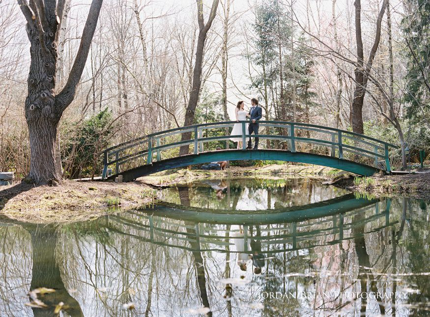 Bride and groom portrait on bridge at Grounds for sculpture wedding