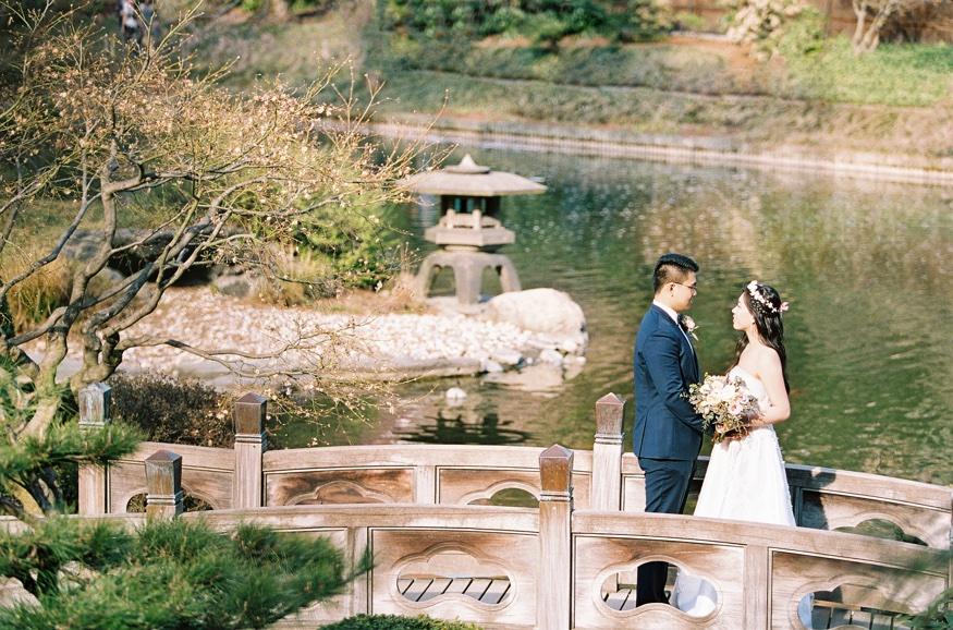 Bride and groom walking through Brooklyn Botanic Gardn wedding at japanese garden